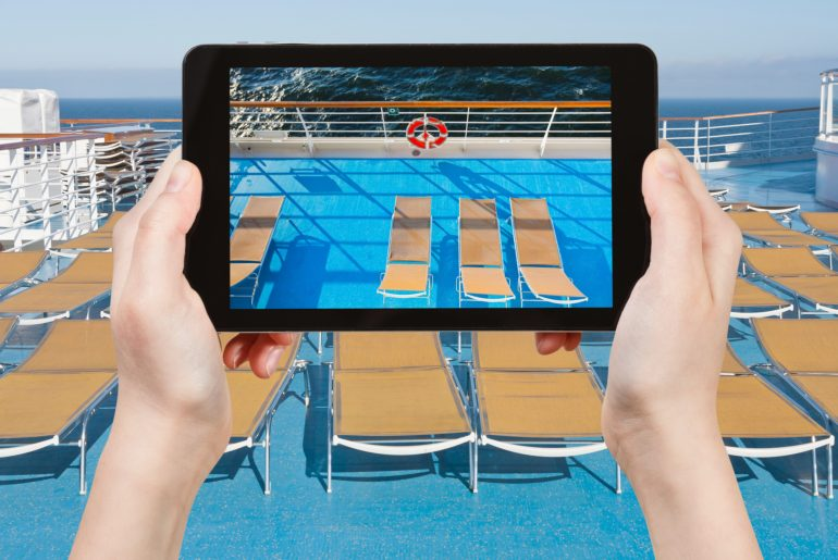 tourist takes picture of sunbath chairs on side of cruise line on smartphone or tablet