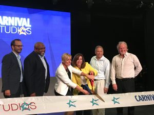 Christine Duffy, in yellow, cutting the ribbon for the new Carnival facility with Sarah Beth Reno, vice president of entertainment.