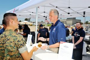 Operation Homefront CEO and President John Pray serves hamburgers to Marines at Carnival Cruise Line's First Ever Socially Powered BBQ at Marine Corps Air Station Miramar on July 5, 2017 in San Diego, California.