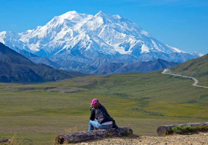 A woman gazes at Mount Denali in Denali National Park and Preserve in Alaska. A look at the highest peak in North America is a highlight on a Holland America Line Alaska Land+Sea Journey.