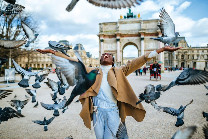 Young smiling woman among doves flying in front of Triumph Arch of Carousel in Paris, France.
