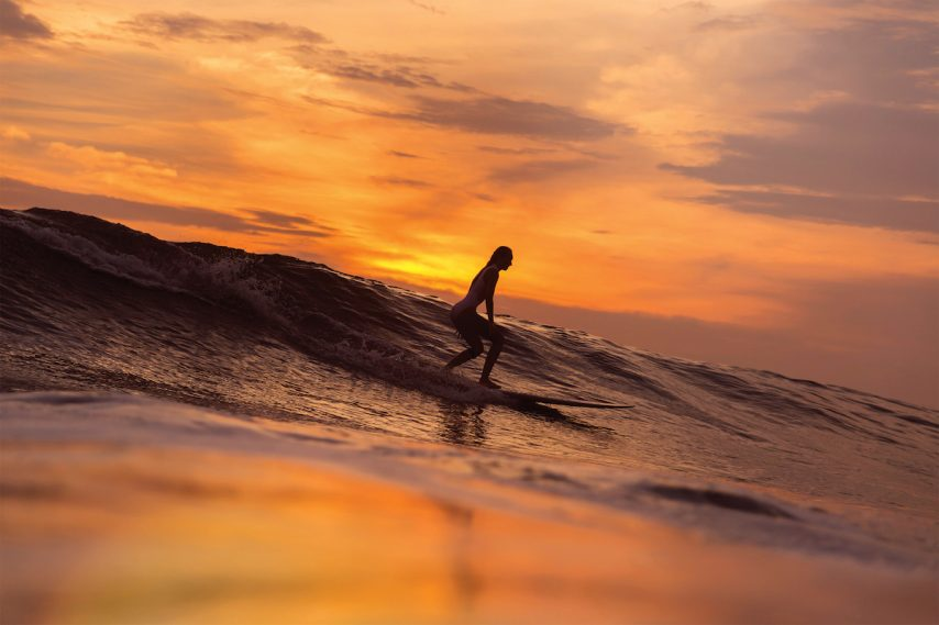 Surfer girl waiting in the line up for a wave at sunrise or sunset